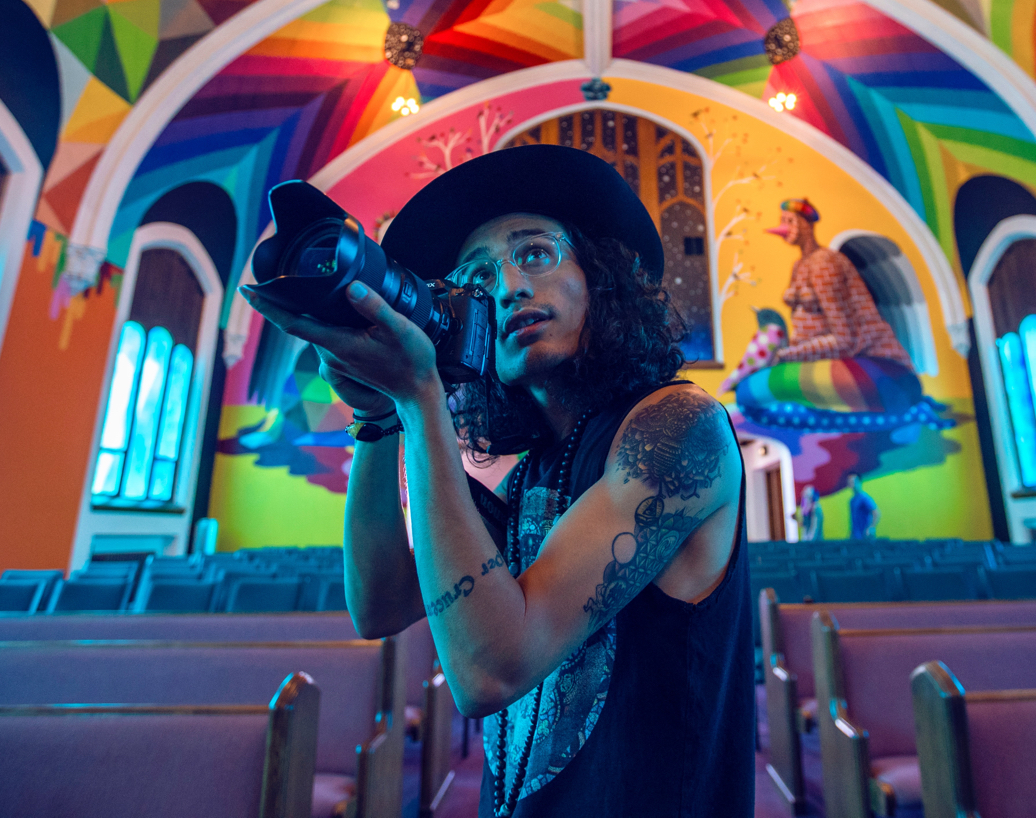 Person holding a camera in a colorful room