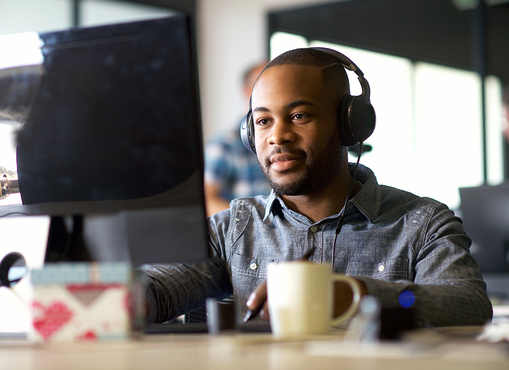 Man with headphones working at a computer