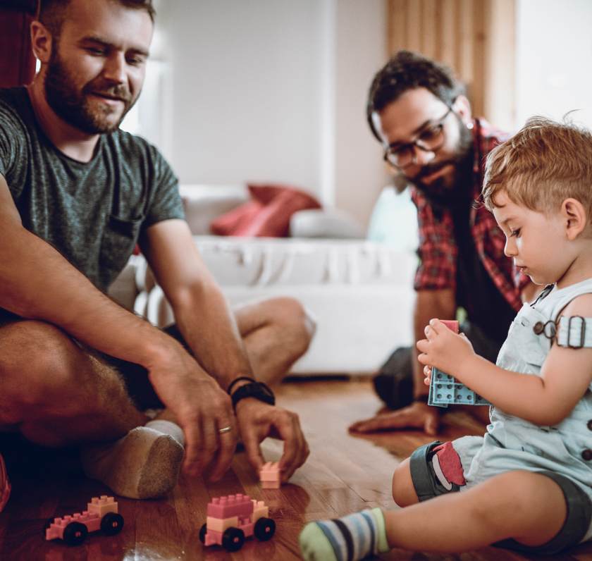 Two men and and child playing with toys on the floor